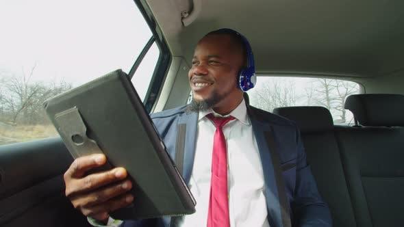 Homme d'affaires positif appréciant la musique dans les écouteurs dans le véhicule