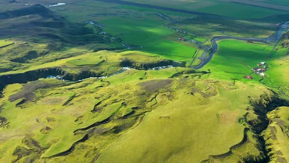 Flying Over Vibrant Green Hills and the River Skogar in Iceland
