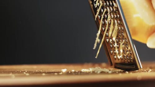 Person Grates Hard Cheese for Pasta on Wooden Board Macro
