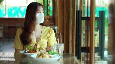 woman with a face mask in restaurant