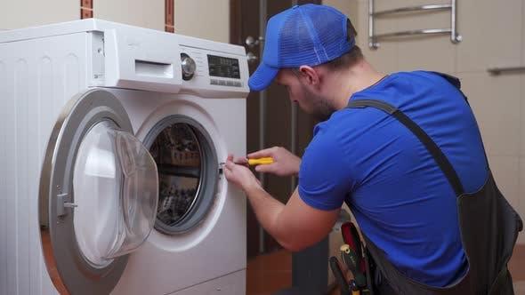 Working Man Plumber Repairs a Washing Machine in Home