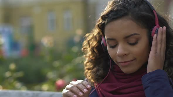 Thumbnail for Close-Up of Happy Female in Headphones Listening Favorite Song Outdoors, Music
