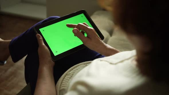 Thumbnail for Aged woman using a digital tablet PC with green screen