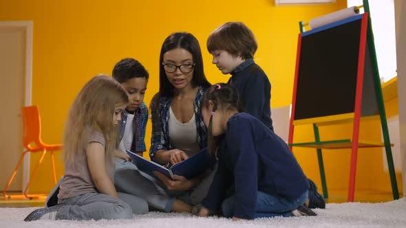 Thumbnail for Preschool Teacher Reading a Book To Diverse Kids