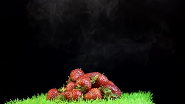 Thumbnail for White smoke covering pile of red strawberries against black background