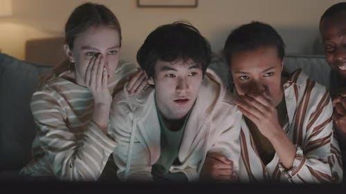 Diverse Friends Watching Thrilling Movie