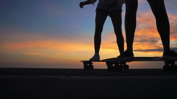 Thumbnail for Close-up of the Legs of Two Girls Girlfriend in Shorts and Sneakers Ride Skateboards on the Slope