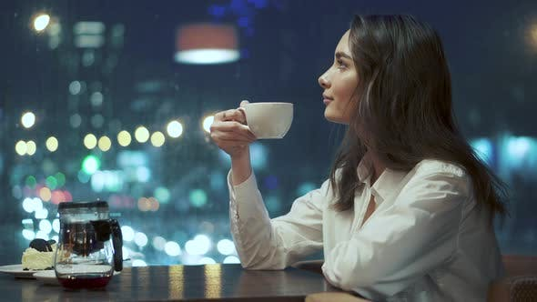 Thumbnail for Girl Drinks Tea and Admires the View of the Night City Sitting in a Cozy Cafe Late in the Evening