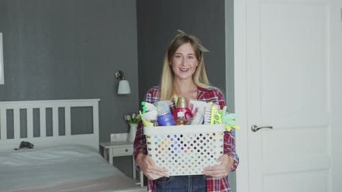 Woman with Basket Full of Sponges and Household Chemicals Look at Camera
