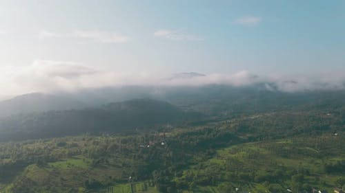 Flight Over the Mountains in the Morning. The Mountain Range on the Horizon Is Covered with Morning