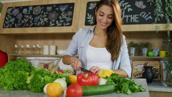 Thumbnail for Attraktive Frau mit charmantem Lächeln Schneiden mit Messer Gelber Pfeffer für Salat in der gemütlichen Küche