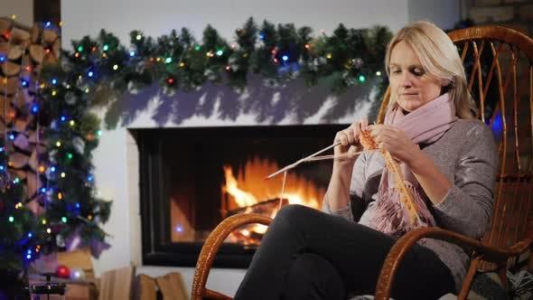 Thumbnail for Ruhe auf einem Winterabend - eine Frau strickt beim Sitzen durch einen Kamin dekoriert für Weihnachten
