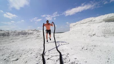 Athlete doing cross fitness workout outdoor. Battle rope training as functional fitness on nature