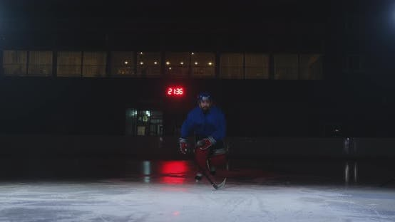 Cover Image for Man Hockey Player in Hockey Uniform Leaves with a Stick in His Hands Out of the Darkness and Looks