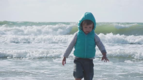 Thumbnail for Toddler Boy in Waistcoat Is Playing with Sand on Sea Side.