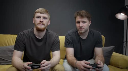 Crazy Fans Of Xbox Sitting on Sofa Emotionally Playing Videogame or Playstation