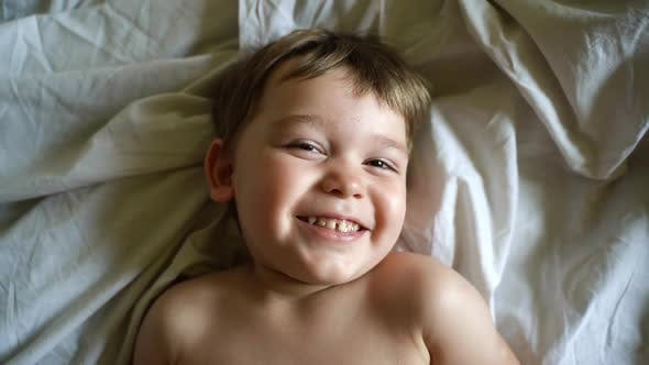 Close-up Portrait of Face of Cheerful Little Boy Lying in Bed on White Sheet and Looks at Camera