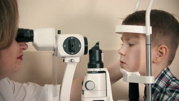 Thumbnail for A Little Boy Having a Treatment in Eye Clinic - a Woman Doctor Checking the Eye Vision By Looking
