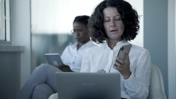 Thumbnail for Ernsthafte Geschäftsfrau mit Smartphone und Laptop
