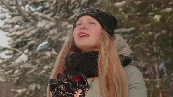 Thumbnail for Mädchen genießt die Schneefälle. Junge Frau in einer gestrickten Form trinkt Tee im Wald während eines