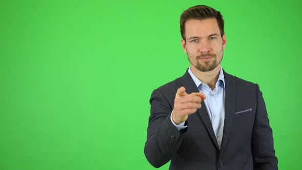 Thumbnail for A Young Handsome Businessman Points at the Camera and Nods with a Smile - Green Screen Studio
