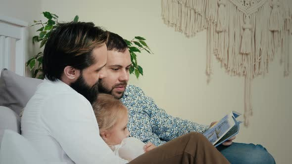 Thumbnail for Homosexual Male Couple lying with daughter in bedroom