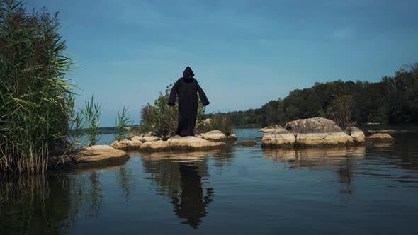 Thumbnail for Evil Witch in Black Cloak with Hood on Stones Near the River