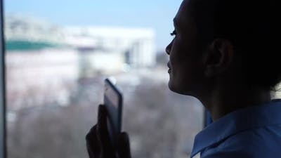 Silhouette of Woman Calling on Cellphone By Window