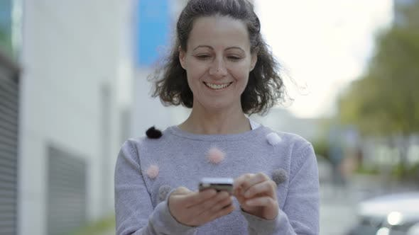 Thumbnail for Front View of Smiling Middle Aged Woman Using Smartphone.