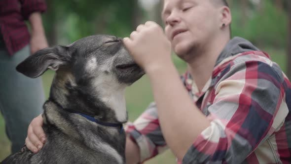 Close-up of Blurred Man Caressing Head of Domestic Dog Outdoors, Happy Smiling Pet Owner Enjoying