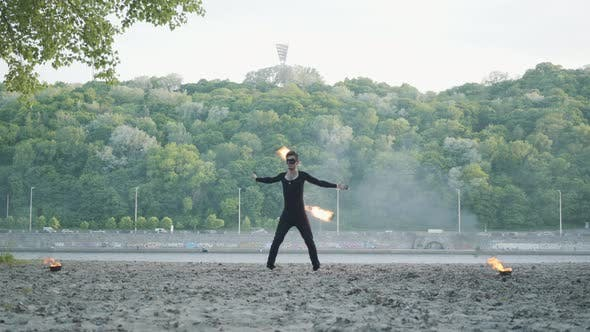 Thumbnail for Young Slim Man in Black Clothes and Mask Performing a Show with Flame Standing on Riverbank
