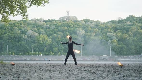 Thumbnail for Junge schlanke Mann in schwarz Kleidung und Maske Durchführung einer Show mit Flamme stehend auf Riverbank