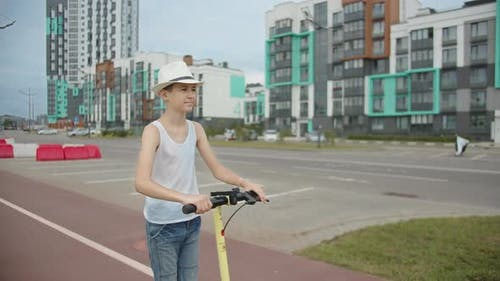 Funny Boy Rides an Electric Scooter Around the City on a Special Road