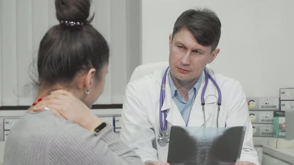 Mature Male Doctor Talking to His Female Patient