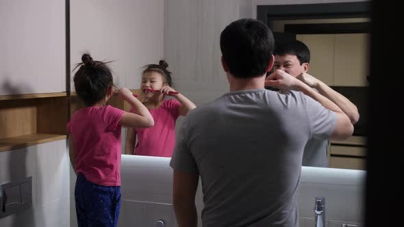 Thumbnail for Asian Dad and Daughter Brushing Teeth in Bathroom