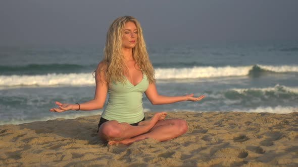 Thumbnail for A young woman doing yoga on the beach while sitting