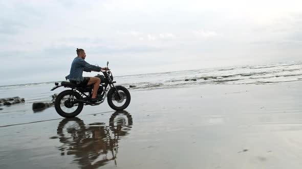 Thumbnail for Man in Riding Motorcycle on Beach. Vintage Motorbike on Beach Sunset on Bali. Young Hipster Male