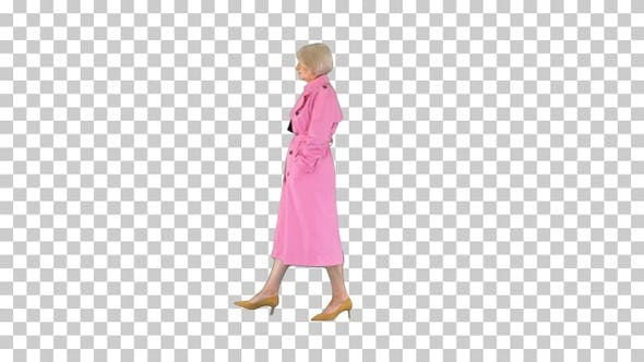 Rich senior woman in pink trench coat walking by, Alpha Channel