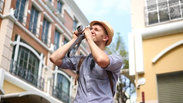 Thumbnail for Young Tourist With Backpack Taking Photos With Camera In City