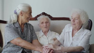 Three Cute Grandmothers Sitting on Sofa Putting Hands on Hands and Smiling