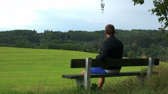 Thumbnail for Young Man Sits on the Bench in Nature (Field with Forest) and Looks Around