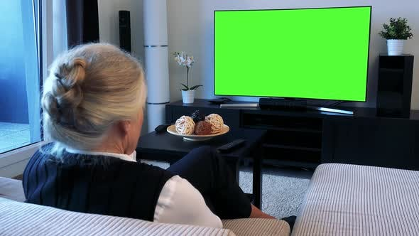 Thumbnail for Old Caucasian Woman Watches Television in Living Room - Green Screen
