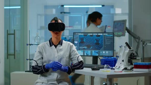 Professional Scientist Wearing Virtual Reality Glasses Using Medical Inovation in Lab