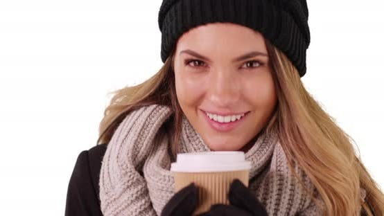 Thumbnail for Closeup of millennial girl in winter wear drinking coffee in studio with copyspace