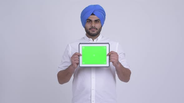 Thumbnail for Happy Young Bearded Indian Sikh Man Showing Digital Tablet