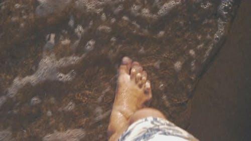 Vacationer walking along the sea coast and waves washing his feet