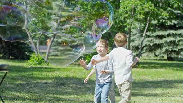 Cover Image for Adorable Little Boys Bursting Giant Soap Bubble during Performance
