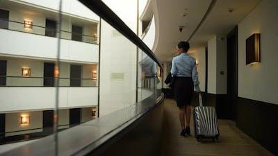 Elegant Businesswoman Walking Along Hotel Balcony