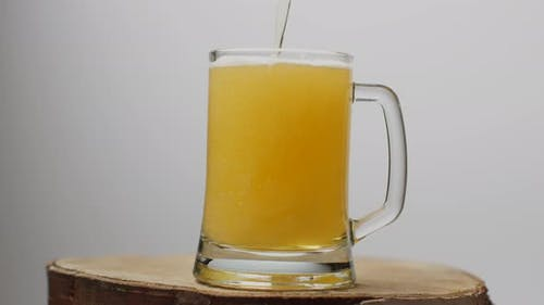Beer Is Poured Into a Beer Glass with a Handle, a Lot of Bubbles and Foam.