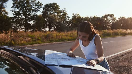 Alone Woman Driver Studying Map on Car Hood, Planning Her Route at Countryside